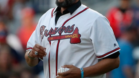 Former Atlanta Braves player David Justice walks onto the field to throw out the ceremonial first pitch before a baseball game between the Braves and the Washington Nationals on Tuesday, April 3, 2018, in Atlanta. (AP Photo/John Bazemore)