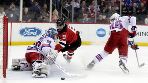 New Jersey Devils left wing Taylor Hall (9) attacks as New York Rangers goaltender Henrik Lundqvist (30), of Sweden, and defenseman Brady Skjei (76) defend during the second period of an NHL hockey game, Tuesday, April 3, 2018, in Newark, N.J. (AP Photo/Julio Cortez)