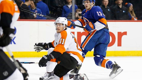New York Islanders center Mathew Barzal (13) watches his goal along with Philadelphia Flyers center Travis Konecny (11) during the second period of an NHL hockey game in New York, Tuesday, April 3, 2018. (AP Photo/Adam Hunger)