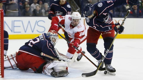 Columbus Blue Jackets' Sergei Bobrovsky, left, of Russia, makes a save as teammate Seth Jones, right, and Detroit Red Wings' Dylan Larkin vie for the puck during the third period of an NHL hockey game Tuesday, April 3, 2018, in Columbus, Ohio. The Blue Jackets won 5-4. (AP Photo/Jay LaPrete)