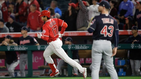 Los Angeles Angels starting pitcher Shohei Ohtani, left, of Japan, rounds the bases after hitting a three-run home run against Cleveland Indians starting pitcher Josh Tomlin during the first inning of a baseball game Tuesday, April 3, 2018, in Anaheim, Calif. (AP Photo/Jae C. Hong)