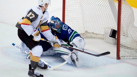 Vegas Golden Knights defenseman Shea Theodore (27) scores past Vancouver Canucks goaltender Jacob Markstrom (25) in the shootout of an NHL hockey game Tuesday, April 3, 2018, in Vancouver, British Columbia. (Jonathan Hayward/The Canadian Press via AP)