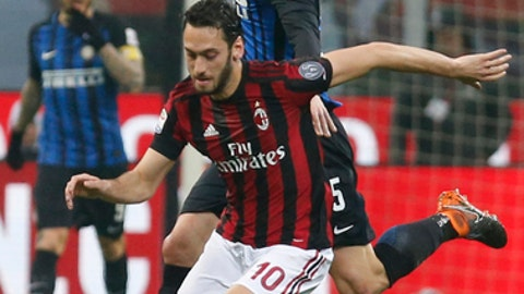 AC Milan's Hakan Calhanoglu, foreground, and Inter Milan's Roberto Gagliardini vie for the ball during an Italian Serie A soccer match between AC Milan and Inter Milan, at the San Siro stadium in Milan, Italy, Wednesday, April 4, 2018. (AP Photo/Antonio Calanni)
