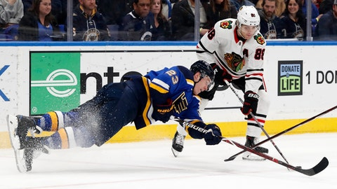 St. Louis Blues' Dmitrij Jaskin, of Russia, dives after a loose puck as Chicago Blackhawks' Patrick Kane (88) watches during the second period of an NHL hockey game Wednesday, April 4, 2018, in St. Louis. (AP Photo/Jeff Roberson)