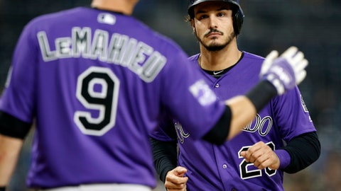 Colorado Rockies' DJ LeMahieu, left, waits to congratulate Nolan Arenado after they scored on a ground-rrule double by Trevor Story during the first inning of a baseball game against the San Diego Padres in San Diego, Wednesday, April 4, 2018. (AP Photo/Alex Gallardo)
