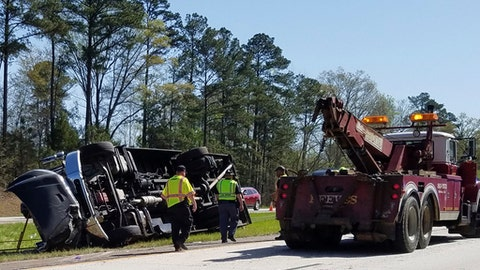 Police officers and emergency workers examine the scene of the accident scene Thursday morning, April 5, 2018, after a tour bus heading to the Masters golf tournament overturned along Interstate 20 near Augusta, Ga. Authorities say at least a dozen people were injured and the bus driver Steven Hoppenbrouwer was charged with DUI. (Joe Hotchkiss/The Augusta Chronicle via AP)