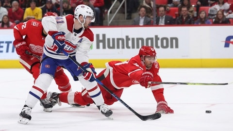 Montreal Canadiens left wing Paul Byron (41) and Detroit Red Wings left wing Darren Helm (43) reach for the puck during the first period of an NHL hockey game Thursday, April 5, 2018, in Detroit. (AP Photo/Carlos Osorio)