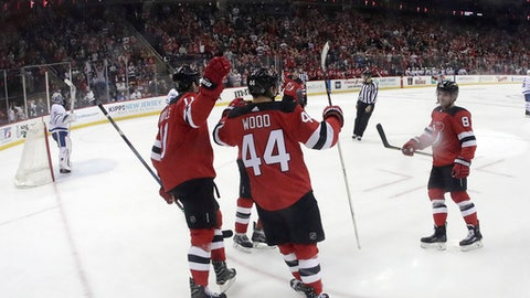 New Jersey Devils players celebrate a goal by left wing Miles Wood (44) during the second period of an NHL hockey game against the Toronto Maple Leafs, Thursday, April 5, 2018, in Newark, N.J. (AP Photo/Julio Cortez)