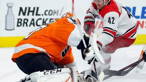 Philadelphia Flyers' Brian Elliott, left, defends as Carolina Hurricanes' Joakim Nordstrom, right, attacks during the third period of an NHL hockey game Thursday, April 5, 2018, in Philadelphia, Pa.  (AP Photo/Tom Mihalek)