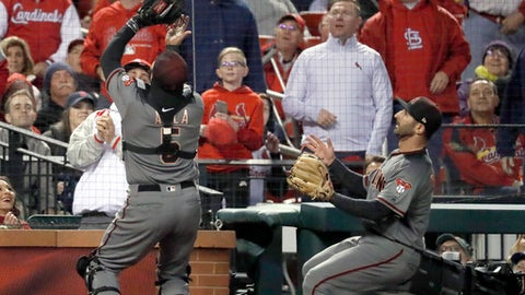 Arizona Diamondbacks catcher Alex Avila, left, catches a foul ball by St. Louis Cardinals' Greg Garcia as Diamondbacks third baseman Daniel Descalso watches during the seventh inning of a baseball game Thursday, April 5, 2018, in St. Louis. (AP Photo/Jeff Roberson)