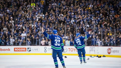 Vancouver Canucks' Henrik Sedin, left, and his twin brother, Daniel Sedin, wave to the crowd after the Canucks defeated the Arizona Coyotes 4-3 in the brothers' last home NHL hockey game, Thursday, April 5, 2018, in Vancouver, British Columbia. (Darryl Dyck/The Canadian Press via AP)