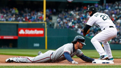 Atlanta Braves' Dansby Swanson, left, slides safely into third base for a triple to drive in two runs as Colorado Rockies third baseman Nolan Arenado turns to apply the tag in the first inning of a baseball game Friday, April 6, 2018, in Denver. (AP Photo/David Zalubowski)