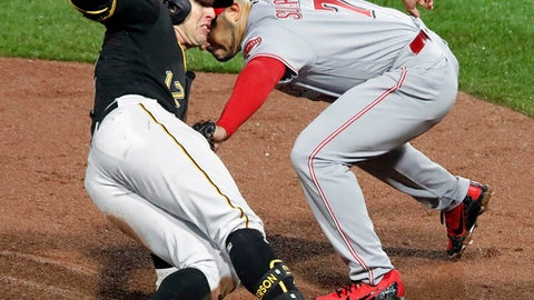 Pittsburgh Pirates' Corey Dickerson (12) is tagged out by Cincinnati Reds third baseman Eugenio Suarez (7) while trying to stretch a double into a triple in the sixth inning of the team's baseball game in Pittsburgh, Friday, April 6, 2018. (AP Photo/Gene J. Puskar)