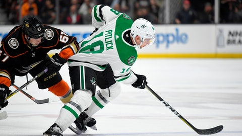 Dallas Stars center Tyler Pitlick, right, passes the puck while under pressure from Anaheim Ducks center Rickard Rakell during the second period of an NHL hockey game Friday, April 6, 2018, in Anaheim, Calif. (AP Photo/Mark J. Terrill)