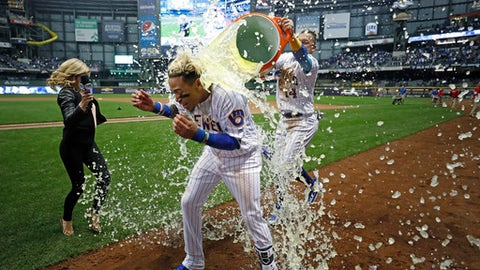 Milwaukee Brewers' Orlando Arcia is doused by Hernan Perez after Arcia drove in the winning run in the ninth inning of a baseball game against the Chicago Cubs on Friday, April 6, 2018, in Milwaukee. (AP Photo/Jeffrey Phelps)