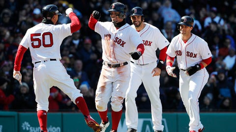 Xander Bogaerts smiles as he is congratulated by Mookie Betts, left, after hitting a grand slam that scored Betts, Andrew Benintendi, right, and J.D. Martinez, second from right, during the second inning of a baseball game against the Tampa Bay Rays at Fenway Park in Boston, Saturday, April 7, 2018. (AP Photo/Winslow Townson)