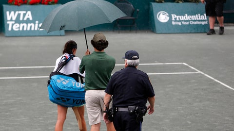 Anastasija Sevastova, from Latvia, leaves the court due to a rain delay in during a semifinal match against Julia Goerges, from Germany, at the Volvo Car Open tennis tournament in Charleston, S.C., Saturday, April 7, 2018. Play was suspended due to rain in the first set with them tied 4-4. (AP Photo/Mic Smith)