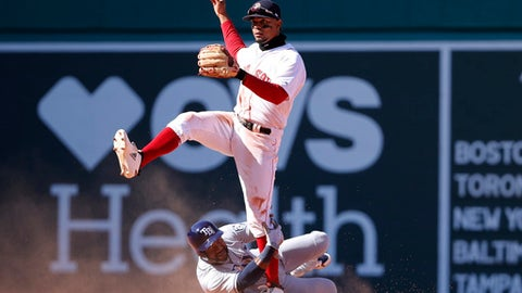 Boston Red Sox shortstop Xander Bogaerts and Tampa Bay Rays' Denard Span look down to first to watch after Bogaerts completed a double play during the eighth inning of Boston's 10-3 win in a baseball game at Fenway Park in Boston Saturday, April 7, 2018. (AP Photo/Winslow Townson)