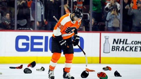 Philadelphia Flyers' captain Claude Giroux skates past hat thrown by fans after he scored his third goal of the game during the third period of an NHL hockey game against the New York Rangers, Saturday, April 7, 2018 in Philadelphia. The Flyers won 5-0. (AP Photo/Tom Mihalek)