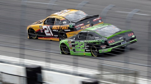 CORRECTS IDS OF BOTH DRIVERS Ryan Blaney (22) makes a passing move against Daniel Hemric (21) going into Turn 2 during a NASCAR XFINITY series auto race in Fort Worth, Texas, Saturday, April 6, 2018. (AP Photo/Tony Gutierrez)