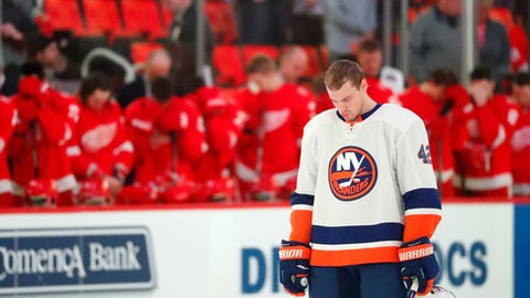 New York Islanders defenseman Scott Mayfield stands near the Detroit Red Wings bench in a moment of silence for the deaths of members of the Humboldt Broncos junior hockey league team, before an NHL hockey game Saturday, April 7, 2018, in Detroit. A crash between a tractor-trailer and the bus carrying the Canadian junior hockey league team from Saskatchewan, Canada, occurred Friday on Highway 35 in Saskatchewan, about 150 miles northeast of Saskatoon (AP Photo/Paul Sancya)