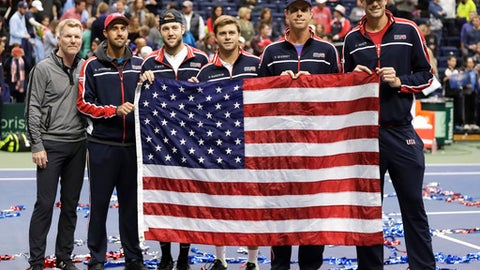 The United States Davis Cup tennis team poses with an American flag after beating Belgium to win their quarterfinal series Saturday, April 7, 2018, in Nashville, Tenn. From left are captain Jim Courier, Steve Johnson, Jack Sock, Ryan Harrison, Sam Querrey and John Isner. (AP Photo/Mark Humphrey)
