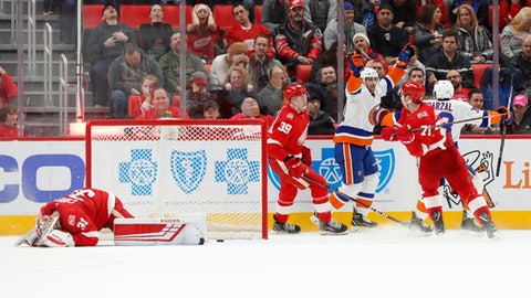 New York Islanders center John Tavares celebrates scoring on Detroit Red Wings goaltender Jared Coreau, left, in overtime of an NHL hockey game Saturday, April 7, 2018, in Detroit. The Islanders won 4-3. (AP Photo/Paul Sancya)