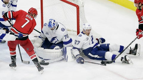 Tampa Bay Lightning's Ryan McDonagh (27) and goalie Louis Domingue (70) defend against Carolina Hurricanes' Derek Ryan (7) during the third period of an NHL hockey game in Raleigh, N.C., Saturday, April 7, 2018. Carolina won 3-2 in overtime. (AP Photo/Gerry Broome)