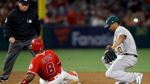 Oakland Athletics shortstop Marcus Semien, right, can't handle the throw from the center field as Los Angeles Angels' Justin Upton slides into second for a double during the sixth inning of a baseball game in Anaheim, Calif., Saturday, April 7, 2018. (AP Photo/Alex Gallardo)