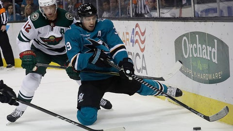 San Jose Sharks center Logan Couture (39) reaches for the puck in front of Minnesota Wild center Eric Staal (12) during the second period of an NHL hockey game in San Jose, Calif., Saturday, April 7, 2018. (AP Photo/Jeff Chiu)