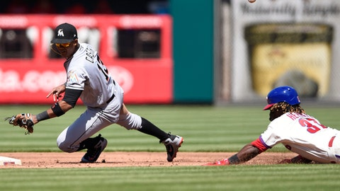 Philadelphia Phillies' Odubel Herrera, right, beats the throw to Miami Marlins second baseman Starlin Castro, left, after hitting a double in the first inning of a baseball game Sunday, April 8, 2018, in Philadelphia. (AP Photo/Michael Perez)