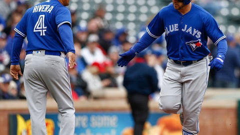 Toronto Blue Jays' Steve Pearce, right, is congratulated by third base coach Luis Rivera (4) as he rounds the bases on his home run off the first pitch thrown by Texas Rangers starting pitcher Cole Hamels during the first inning of a baseball game, Sunday, April 8, 2018, in Arlington, Texas. (AP Photo/Jim Cowsert)