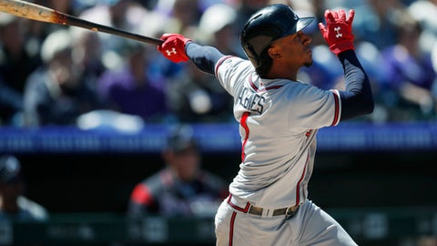 Atlanta Braves' Ozzie Albies follows the flight of his RBI-double off Colorado Rockies starting pitcher Kyle Freeland in the fifth inning of a baseball game Sunday, April 8, 2018, in Denver. (AP Photo/David Zalubowski)
