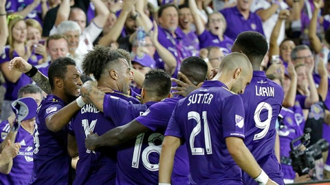 Orlando City's Giles Barnes, second from left, celebrates after scoring a goal with teammates, including Dom Dwyer (18), Scott Sutter (21) and Cyle Larin (9), during the second half of an MLS soccer match against Columbus Crew, Saturday, Aug. 19, 2017, in Orlando, Fla. (AP Photo/John Raoux)