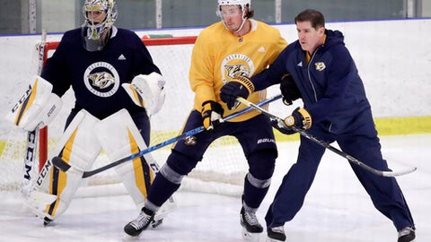 Nashville Predators head coach Peter Laviolette, right, runs a drill with center Ryan Johansen and goalie Juuse Saros, of Finland, left, during a practice Monday, April 9, 2018, in Nashville, Tenn. The Predators are scheduled to play the Colorado Avalanche in the first round of the NHL Western Conference hockey playoffs on Thursday. (AP Photo/Mark Humphrey)