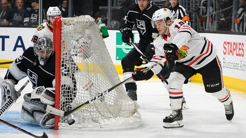 FILE - In this March 3, 2018, file photo, Chicago Blackhawks right wing Alex DeBrincat, right, tries to center the puck behind the net as Los Angeles Kings goalie Jonathan Quick defends during an NHL hockey game in Los Angeles. Blackhawks general manager Stan Bowman has said the teams top priority is keeping the young players who have impressed this season, including rookie DeBrincat. (AP Photo/Michael Owen Baker, File)
