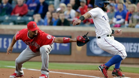Los Angeles Angels designated hitter Albert Pujols attempts to tag out Texas Rangers' Rougned Odor who got back to first safely after Elvis Andrus lined out to right in the first inning of a baseball game in Arlington, Texas, Monday, April 9, 2018. Odor suffered and unknown injury on the play and left the game. (AP Photo/Tony Gutierrez)