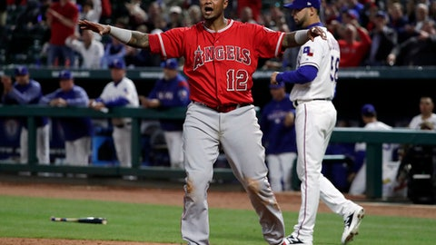 Los Angeles Angels' Martin Maldonado (12) yells to the dugout that he was safe as Texas Rangers relief pitcher Alex Claudio, rear, watches following a close call at the plate in which Maldonado was ruled out in the sixth inning of a baseball game in Arlington, Texas, Monday, April 9, 2018. The call was reversed after a video review. (AP Photo/Tony Gutierrez)