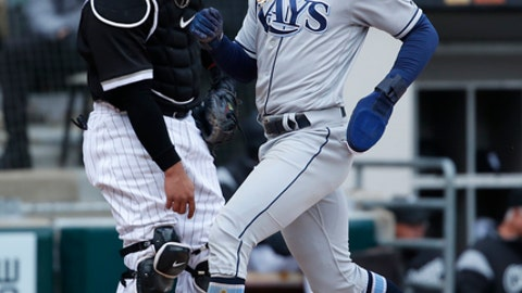 Tampa Bay Rays center fielder Mallex Smith, right, scores a run as Chicago White Sox catcher Welington Castillo (21) stands at the plate during the fourth inning of a baseball game in Chicago on Tuesday, April 10, 2018. (AP Photo/Jeff Haynes)