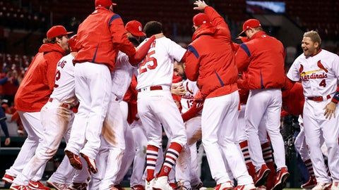 St. Louis Cardinals' Matt Carpenter (13) is surrounded by teammates as he steps on home after hitting a walk-off home run during the 11th inning of a baseball game against the Milwaukee Brewers on Tuesday, April 10, 2018, in St. Louis. The Cardinals won 5-3. (AP Photo/Jeff Roberson)