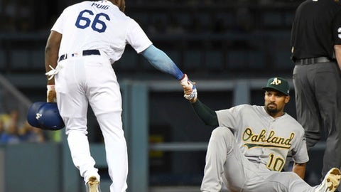 Los Angeles Dodgers' Yasiel Puig, left, helps up Oakland Athletics shortstop Marcus Semien after Semien tagged out Puig in the fifth inning of a baseball game Tuesday, April 10, 2018, in Los Angeles. (AP Photo/Michael Owen Baker)
