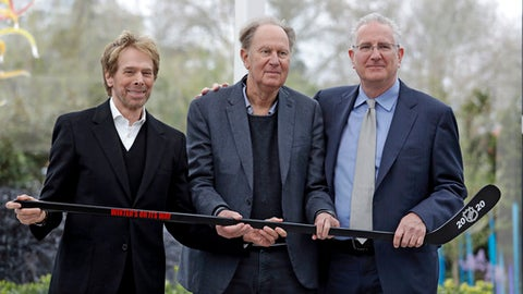 Part owners Jerry Bruckheimer, left, and David Bonderman, center, pose with Tod Leiweke and a hockey stick during a news conference naming Leiweke as the president and CEO for a prospective NHL expansion team, Wednesday, April 11, 2018, in Seattle. Leiweke is the brother of Tim Leiweke, the CEO of the group heading the redevelopment of the arena which would serve as a home for a new hockey team. The group is seeking to have a team awarded in time to begin play in 2020. (AP Photo/Elaine Thompson)