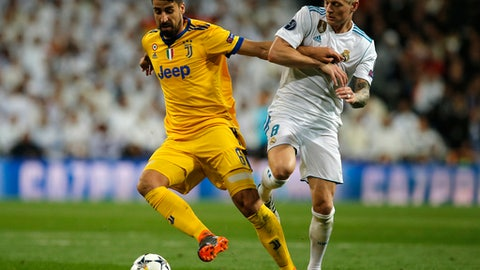 Juventus' Sami Khedira, left, is challenged by Real Madrid's Toni Kroos during a Champions League quarter-final, 2nd leg soccer match between Real Madrid and Juventus at the Santiago Bernabeu stadium in Madrid, Spain, Wednesday, April 11, 2018. (AP Photo/Paul White)