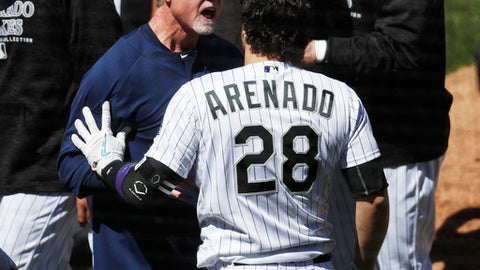 San Diego Padres bench coach Mark McGwire, left, restrains Colorado Rockies' Nolan Arenado after he charged the mound following getting hit by a pitch from Padres starting pitcher Luis Perdomo in the third inning of a baseball game Wednesday, April 11, 2018, in Denver. (AP Photo/David Zalubowski)