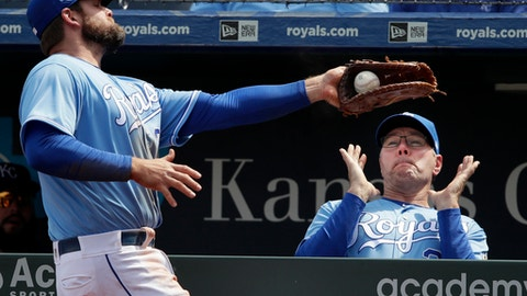 Kansas City Royals first baseman Lucas Duda, left, catches a foul ball near the dugout hit by Seattle Mariners' Guillermo Heredia during the fourth inning of a baseball game at Kauffman Stadium in Kansas City, Mo., Wednesday, April 11, 2018. Kansas City Kansas City Royals pitching coach Cal Eldred, right, gets out of the way. (AP Photo/Orlin Wagner)