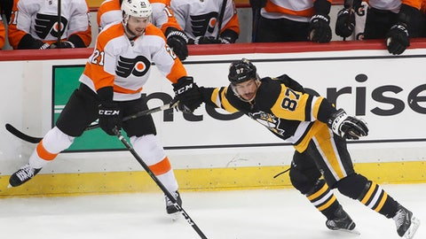 Philadelphia Flyers' Scott Laughton (21) hangs onto Pittsburgh Penguins' Sidney Crosby (87) during the first period in Game 1 of an NHL first-round hockey playoff series in Pittsburgh, Wednesday, April 11, 2018. (AP Photo/Gene J. Puskar)