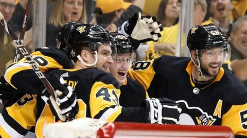 Pittsburgh Penguins' Jake Guentzel, center, celebrates his goal with teammates during the second period in Game 1 of an NHL first-round hockey playoff series against the Philadelphia Flyers in Pittsburgh, Wednesday, April 11, 2018. (AP Photo/Gene J. Puskar)