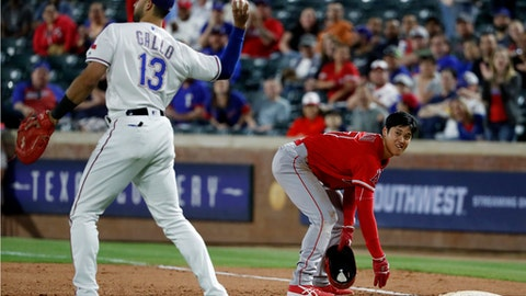 Texas Rangers' Joey Gallo tosses the ball after tagging out Los Angeles Angels' Shohei Ohtani on a pick off by Rangers relief pitcher Chris Martin in the eighth inning of a baseball game in Arlington, Texas, Wednesday April 11, 2018. (AP Photo/Tony Gutierrez)