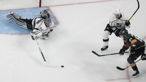 Los Angeles Kings goaltender Jonathan Quick (32) dives to block the puck in front of Vegas Golden Knights center Jonathan Marchessault (81) during the first period of Game 1 of an NHL hockey first-round playoff series, Wednesday, April 11, 2018, in Las Vegas. (AP Photo/John Locher)