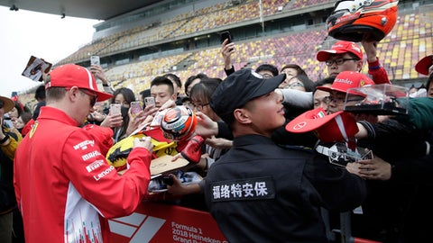 A security guard tries to hold barricades as Ferrari driver Kimi Raikkonen of Finland signs his autograph for fans at the Shanghai International Circuit ahead of the Chinese Formula One Grand Prix in Shanghai, Thursday, April 12, 2018. (AP Photo/Andy Wong)